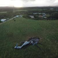 An image captured by a drone Thursday shows the remains of a U.S. military CH-53E helicopter in a field in Higashi, Okinawa Prefecture, after a midair fire and crash-landing the previous day. | KYODO