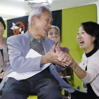 Nobuo Miyake (center), a survivor of the 1945 Hiroshima bombing, expresses joy after the announcement of the winner of the 2017 Nobel Peace Prize in Tokyo on Friday. | KYODO