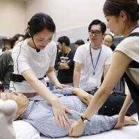 Nurse Saki Ishikawa (left) teaches care staff how to attend to a patient with dementia using the care-giving method called 'humanitude' at a workshop in Tokyo in June. | KYODO