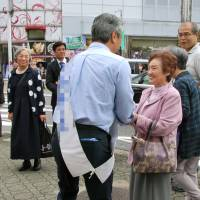 A candidate running for a seat in the Oct. 22 Lower House election reaches out to voters on Friday near Tomio Station, within the No. 1 Nara electoral district.   KYODO