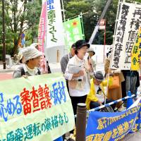 Anti-nuclear activists protest Wednesday in Tokyo after listening to the Nuclear Regulation Authority's decision to allow the restart of two reactors at the Kashiwazaki-Kariwa nuclear complex in Niigata Prefecture. | KYODO