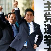 Prime Minister Shinzo Abe and fellow members of his conservative Liberal Democratic Party raise fists at party headquarters in Tokyo on Thursday as they pledge to win the upcoming Lower House election. | REUTERS
