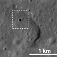 This undated satellite photo taken by the lunar orbiter Kaguya shows a 50-meter hole on the moon's surface that leads to a 50-km-long cave. | JAPAN AEROSPACE EXPLORATION AGENCY / VIA KYODO