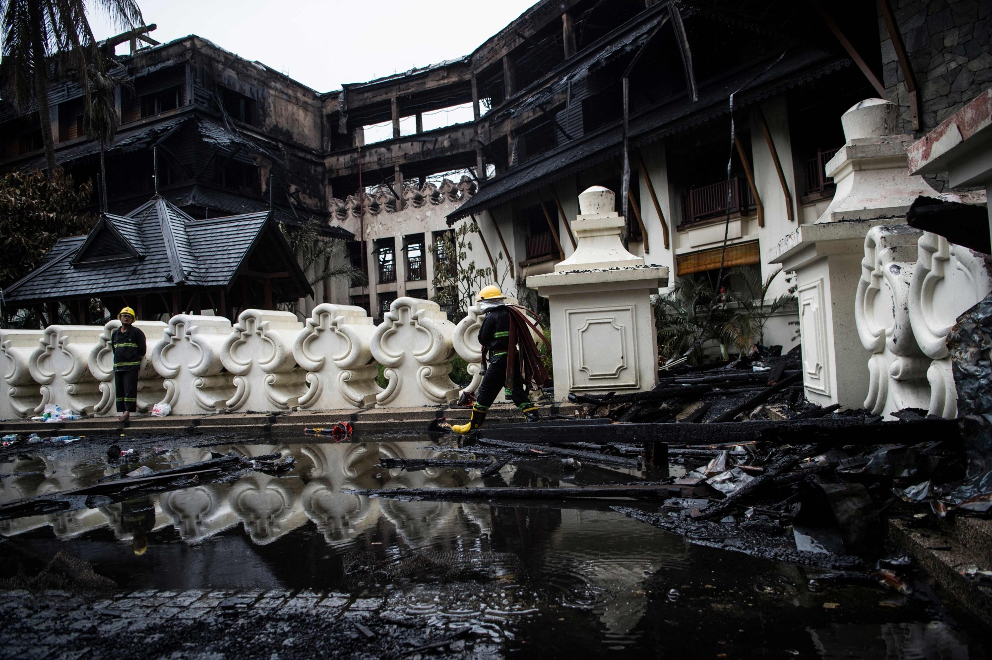 Firefighters work at the scene after a fire guts the Kandawgyi Palace hotel in Yangon on Thursday. | AFP-JIJI
