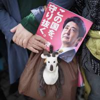 A woman holds an electoral leaflet showing Prime Minister Shinzo Abe during a campaign rally in the city of Saitama on Wednesday. | AFP-JIJI
