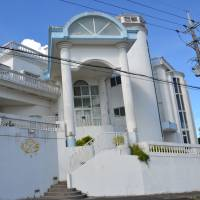 Hotel Sha La La, located amid fields of chrysanthemums grown through light cultivation, attracts inbound tourists with its castle-like exterior. | THE OKINAWA TIMES