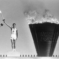 An Olympic torch is lit on Oct. 10, 1964, during the opening ceremony of the 1964 Tokyo Olympics at the National Stadium. It has emerged that the flame from the torch, which was said to have been kept alight since then, actually went out four years ago. | KYODO