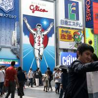 People pose for a selfie in front of the famous 'Glico Man' advertisement in the Dotonbori district in Osaka on Oct. 9. | BLOOMBERG