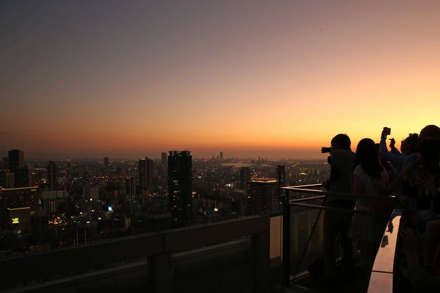 People take photographs from the Umeda Sky Building observation deck at dusk in Osaka on Oct. 9