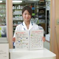 Haruka Hirose, a pharmacist at Nozomi pharmacy in Tokyo's Koto Ward, shows a point-and-speak conversation notebook she compiled for pharmacies to communicate with foreign customers. | KYODO