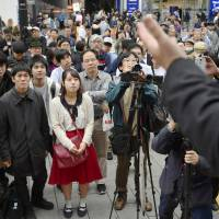 Voters listen to a party leader deliver a speech in Shinjuku Ward, Tokyo, on Saturday during campaigning for the Lower House election. | KYODO