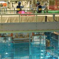 Plutonium-uranium mixed oxide fuel is put into a spent nuclear fuel pool at the Takahama nuclear power plant in Fukui Prefecture on Sept. 28. The fuel will be loaded into a nuclear reactor next year at the earliest. | POOL / VIA KYODO