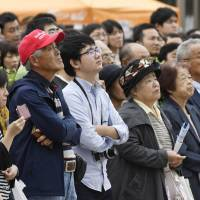 Voters listen to a stump speech being delivered by a candidate for the Oct. 22 Lower House election Saturday in the city of Nagoya. | KYODO