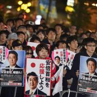 People listen to Prime Minister Shinzo Abe deliver a speech in Tokyo on Friday for Sunday's Lower House election. | AFP-JIJI
