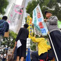 Anti-nuclear activists protest on Wednesday near a building in Tokyo's Minato Ward, where the Nuclear Regulation Authority held a meeting to give safety approval for two reactors at Tepco's Kashiwazaki-Kariwa nuclear power plant in Niigata Prefecture. | KYODO