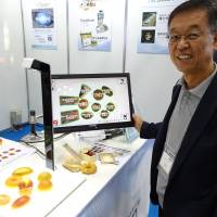 Hisashi Kanbe, CEO of a Hyogo-based company Brain Co., shows a BakeryScan image-recognition checkout system at an exhibition for automatic identification technologies at Tokyo Big Sight in Koto Ward on Sept. 15. | SHUSUKE MURAI