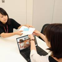 An official at Tokyo-area pub operator United & Collective Co. (left) gives a health insurance card to a new employee in August. | KYODO