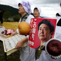 A woman holds a leaflet from the Liberal Democratic Party's election campaign featuring Prime Minister Shinzo Abe's photo while waiting for a campaign rally in the city of Fukushima on Tuesday. | REUTERS