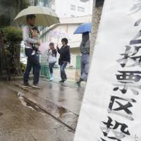 Voters are seen outside a polling station in Sumida Ward, Tokyo, on Sunday amid heavy rain as Typhoon Lan edged closer to the capital. | KYODO