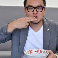 Toshiyuki Kiyomiya, president and chief operating officer of Chikaranomoto Holdings Co., the company that runs the Ippudo ramen chain, mimmicks eating a bowl of ramen on Sept. 29 in Tokyo's Ginza district. | YOSHIAKI MIURA