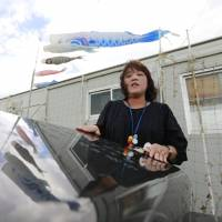 Yuko Tanno, a survivor of the 2011 earthquake and tsunami, talks about her son, Kota, who died in the disaster at age 13, at a monument to him and 13 other students in the Yuriage district of Natori, Miyagi Prefecture, on Sept. 30. | KYODO