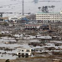 Arahama Elementary School, one of only a handful of buildings to survive the 2011 tsunami in the Arahama district on the outskirts of Sendai, is seen in a photo from the day after the massive tsunami. | KYODO