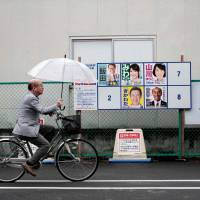 A man cycles past posters of candidates for Sunday's general election in Koshigaya, Saitama Prefecture, on Saturday. A typhoon is expected to lash Japan with heavy rain on Sunday that is likely to weigh on turnout. | AFP-JIJI
