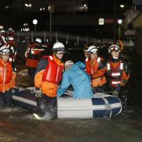 Rescue workers tow a rubber boat carrying an eldery man who was stranded in torrential rain early Monday in Sakai, Osaka Prefecture. | KYODO