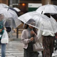 Amid rain and strong winds from Typhoon Saola on Sunday, people use their umbrellas in front of Nagoya Station. | KYODO
