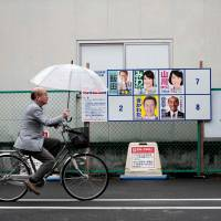 A man walks past electoral posters of candidates for the upcoming election in Koshigaya, Saitama Prefecture, on Oct. 20. | AFP-JIJI