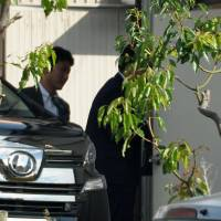 Police investigators enter the office of a company operating the Ripple cryptocurrency exchange in Hamamatsu, Shizuoka Prefecture, on Wednesday. Police arrested the same day Yuki Takenaka, the founder and head of the company, for allegedly swindling ¥1.4 million from a depositor. | KYODO