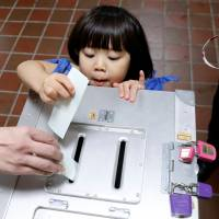 A girl helps her father cast his ballot in Tokyo on Sunday morning. | REUTERS