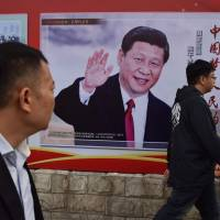 People walk past a poster featuring Chinese President Xi Jinping with a slogan reading 'Chinese Dream, People's Dream' in Beijing on Monday. | AFP-JIJI
