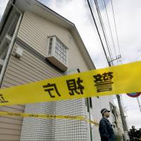A police officer stands guard in front of an apartment building in Zama, Kanagawa Prefecture, where police found nine bodies on Tuesday. | KYODO