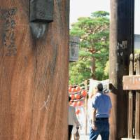 A column of a gate at Zenkoji Temple in Nagano Prefecture is seen vandalized with an 'X' mark on Monday. | KYODO