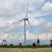 People walk past a turbine at the Electric Power Development Co. wind farm near the city of Koriyama, Fukushima Prefecture in August 2012. | BLOOMBERG