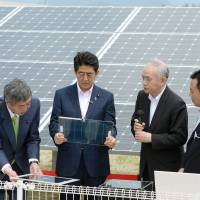Power play: Officials from a research facility in Fukushima Prefecture show Prime Minister Shinzo Abe some solar panels in May 2015. | KYODO