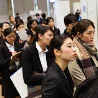 University students line up for a job fair at the Makuhari Messe convention center in the city of Chiba on March 1. Japan's demographics are forcing the nation's corporations to become global front-runners in designing the future of work, and the current young generation is poised to be better off than their parents. | BLOOMBERG