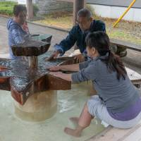 Hot stuff: Visitors relax at one of many free footbaths along the Shiobara Valley. | STEPHEN MANSFIELD