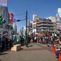 Members of Kibo no To (Party of Hope) rally the crowd during a campaign stop in Tokyo on Tuesday ahead of the Oct. 22 Lower House election. | BLOOMBERG