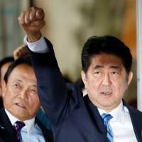 Prime Minister Shinzo Abe and other Liberal Democratic Party lawmakers, including Taro Aso (left), pledge to win in the upcoming election during a rally at LDP headquarters in Tokyo on Sept. 28. Tokyo Gov. Yuriko Koike's new party Kibo no To has energized the opposition. | REUTERS