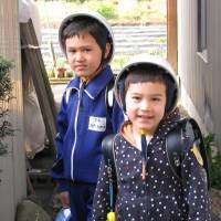 Hard-hat policy: In rural Gifu Prefecture, the author's sons were required to wear hard helmets for the five-minute walk to and from school. Rules such as these didn't go down well with Vincent (left), so his parents decided to enroll him in a Vermont-based virtual school rather than the local junior high. | JOHN SPIRI
