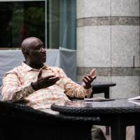 Kyoto Seika University President-elect Oussouby Sacko speaks with writer Baye McNeil in Tokyo. | NICHOLAS SEAGREAVES