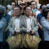 Voters listen to a politician speak in Tokyo on Tuesday, the first day of official campaigning for the Oct. 22 election. | REUTERS