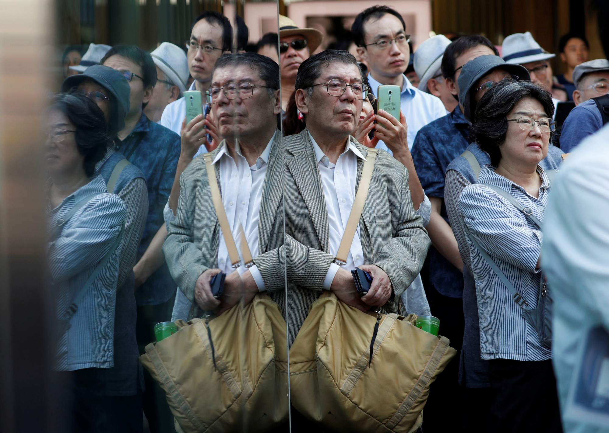 Voters listen to a politician speak in Tokyo on Tuesday, the first day of official campaigning for the Oct. 22 election.   REUTERS