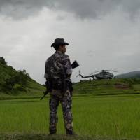 A policeman stands guard on Sept. 27 near a military transport helicopter at Ye Baw Kyaw village in Myanmar's northern Rakhine state, where the Myanmar Army claims Rohingya militants massacred scores of Hindu villagers. | AFP-JIJI