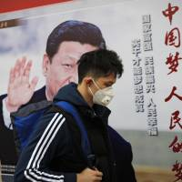 A man wearing an air pollution mask passes by a poster of Chinese President Xi Jinping featuring the phrase 'China Dream, People Dream' on Thursday in Beijing. | AP
