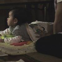 Sleep tight: A baby gets ready to sleep at a nighttime nursery featured in the film 'Yakan mo Yatteru Hoikuen.' | KYODO, © YAKAN MO YATTERU HOIKUEN