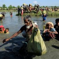 Rohingya refugees who fled from Myanmar make their way after crossing the border in Palang Khali, Bangladesh, on Oct. 16, joining hundreds of thousands of refugees already there. | REUTERS