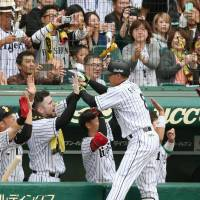 The Tigers' Kosuke Fukudome is congratulated by teammates after hitting a two-run homer in the sixth inning against the BayStars on Saturday in Game 1 of the Central League Climax Series First Stage at Koshien Stadium. Hanshin beat Yokohama 2-0. | KYODO